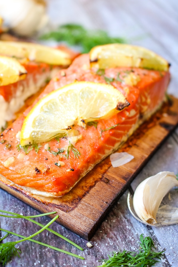 Slice filet of grilled cedar plank salmon, on charred plank with lemon slices.