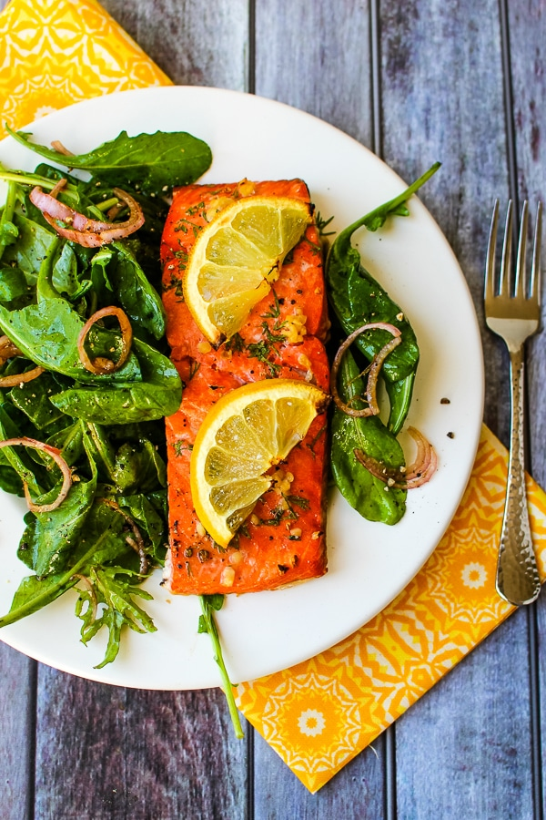 Salmon filet plated with a spinach salad with shallots on the side.
