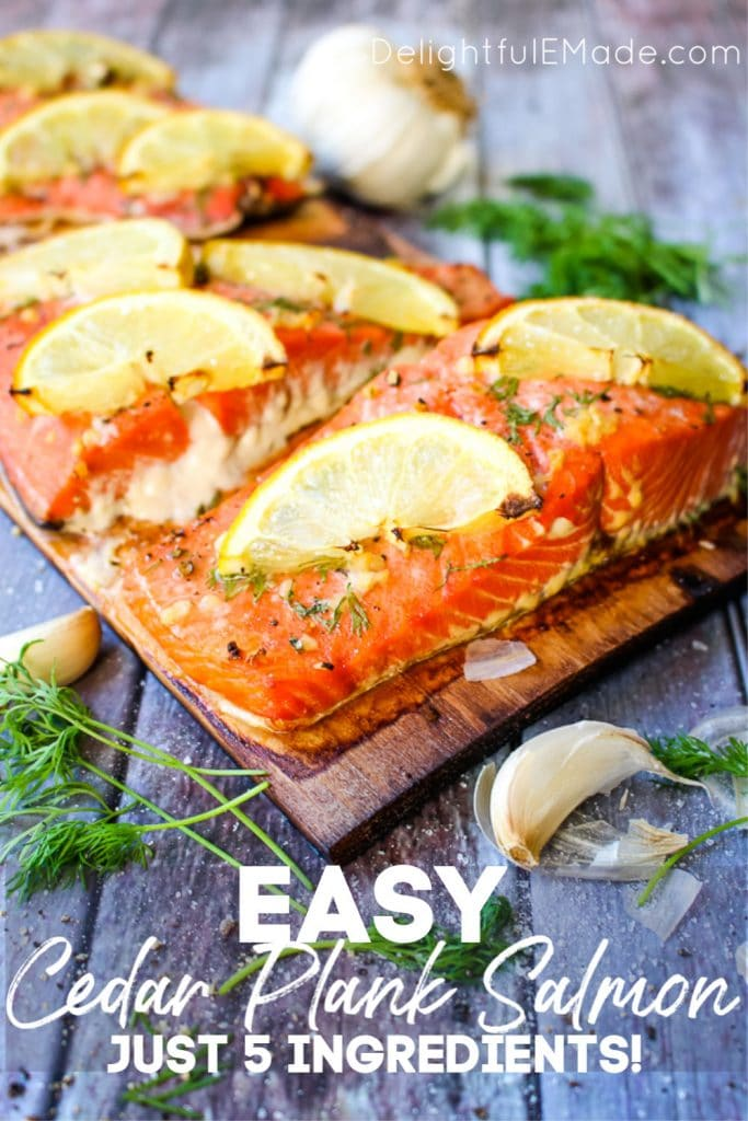 Grilled Cedar Plank Salmon on charred plank, topped with dill, garlic and lemon slices.