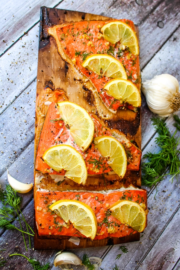 Full plank of cedar plank salmon, three filets topped with lemon slices and dill.