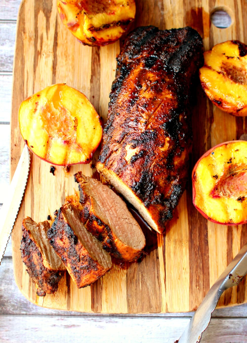 Grilled pork loin recipe, sliced on board with grilled peaches.