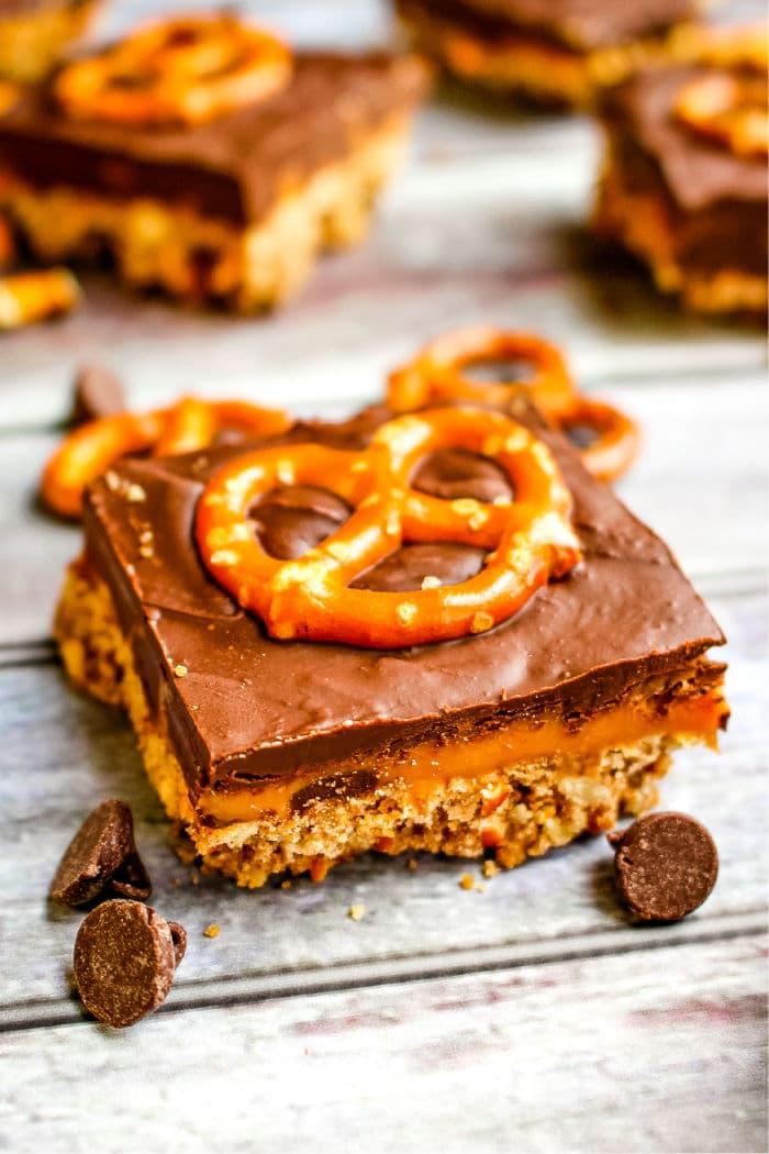 Close up of a single chocolate caramel pretzel bar, cut into a square.