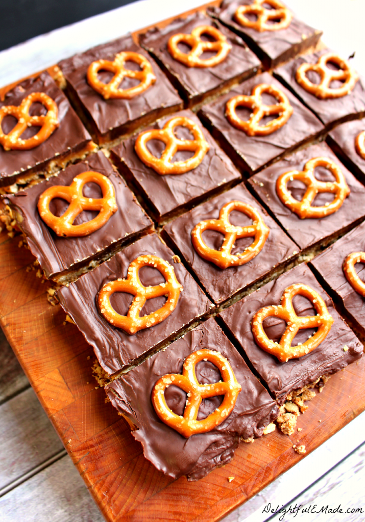 Anyone that loves a sweet & savory treat will love these bars!  A pretzel pecan crust is topped with dark chocolate chips, caramel and topped with more dark chocolate and a pretzel.