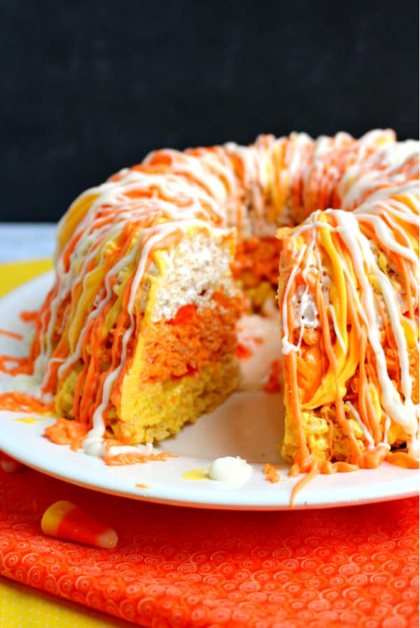 Whole candy corn krispie cake, with one slice missing to show internal yellow, orange and white layers.