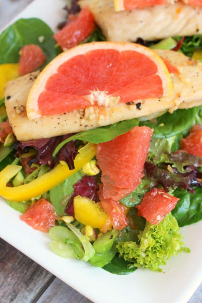 Grapefruit salad with mahi mahi salad, on plate with yellow peppers and pistachios.