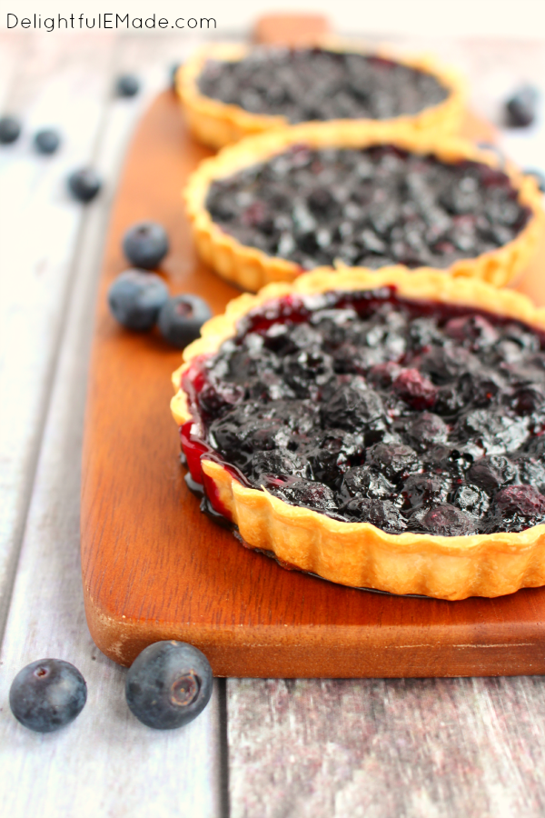 These Blueberry Tarts are as easy as pie, and taste even better!  Topped with a delicious Lemon Mascarpone Cream, these mini-tarts are the perfect dessert for any occasion!