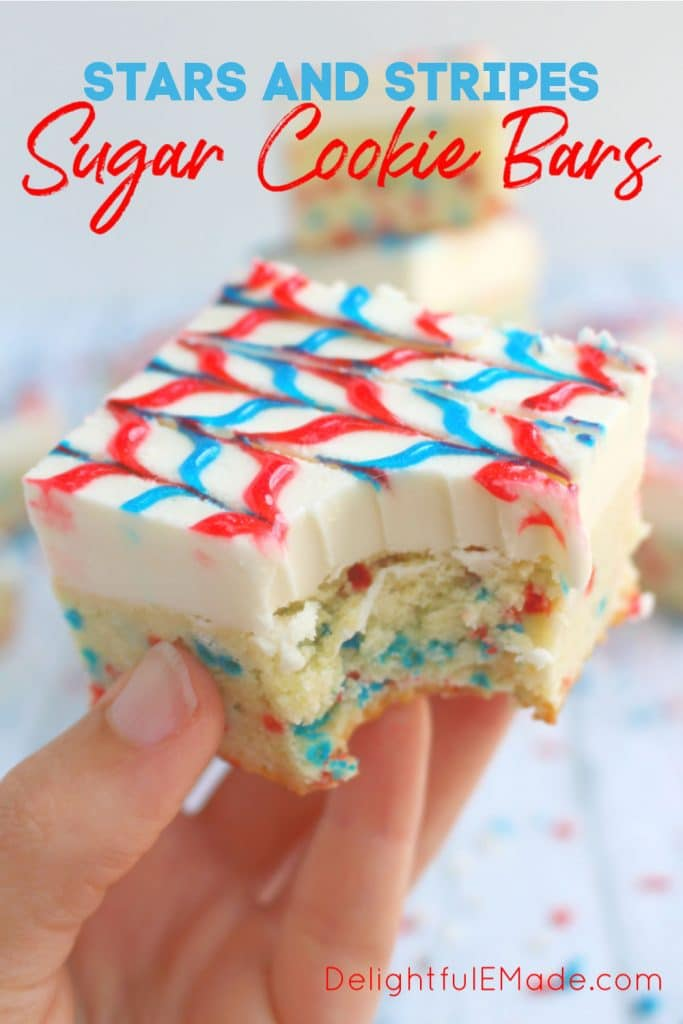 Frosted sugar cookie bar with bite taken out of it. Decorated with red and blue stripes and red white and blue sprinkles.
