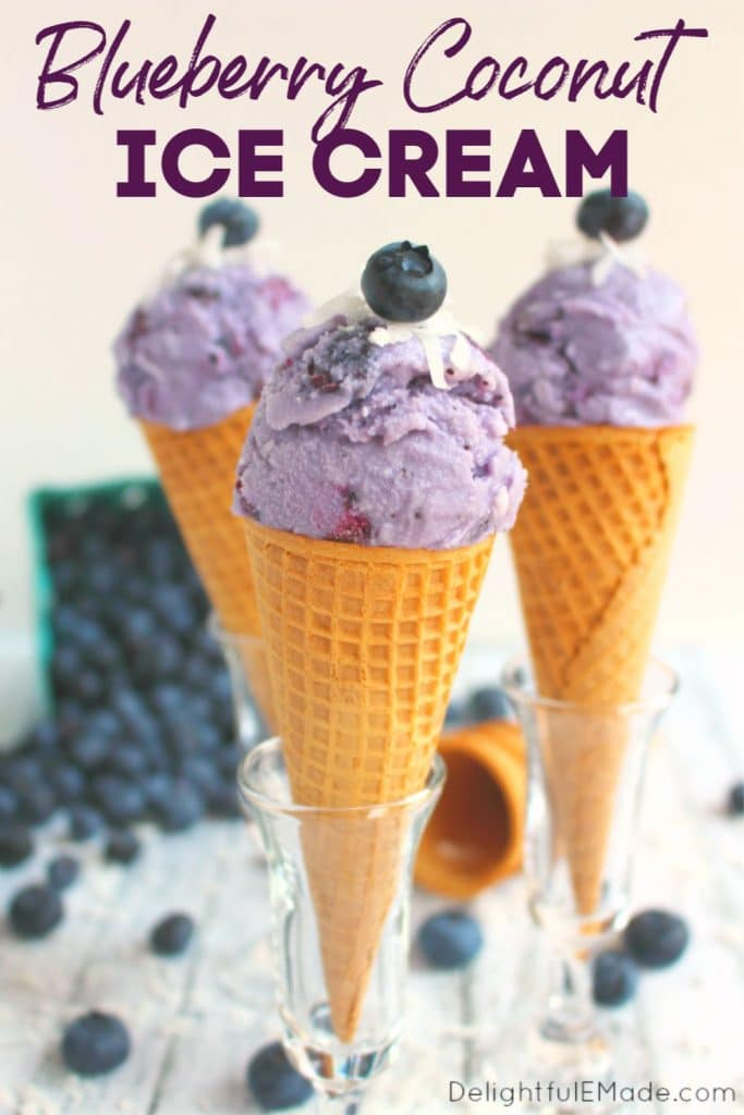 Three ice cream cones topped with a single scoop of blueberry ice cream, and topped with coconut and fresh blueberries.