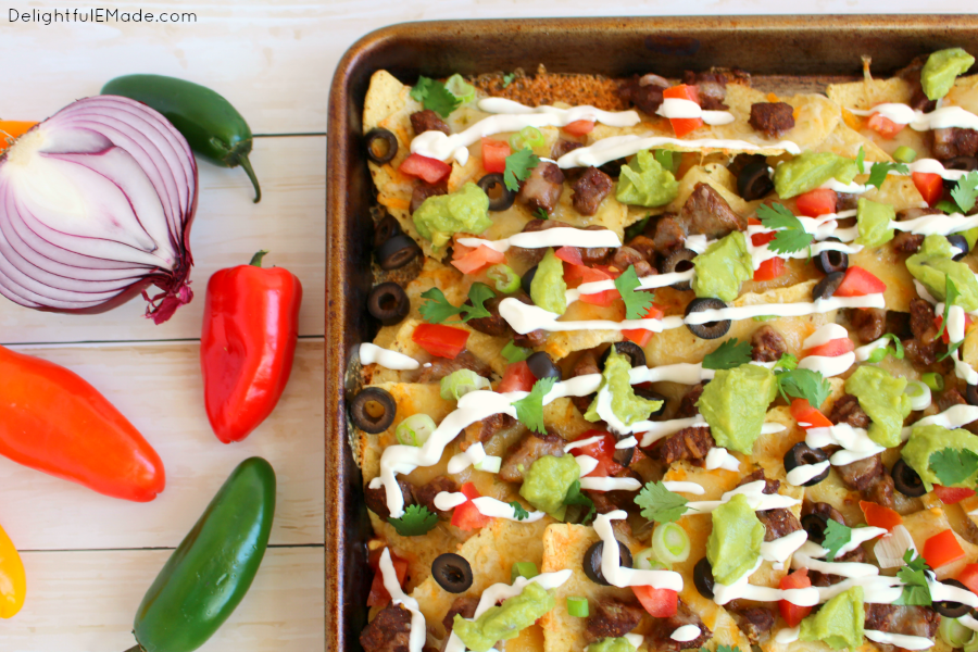 Football food at its finest!  These Loaded Steak Nachos have everything you love stacked on top - loads of cheese, seasoned steak, tomatoes, onions, guacamole and more!  Eat 'em while their hot and make another batch for the second half!