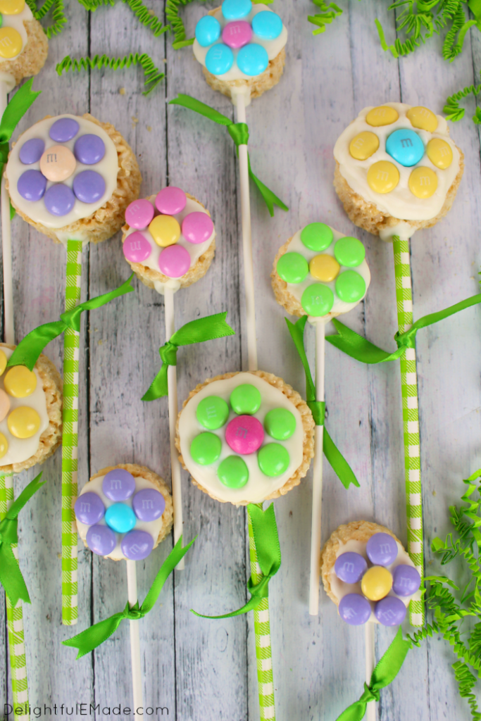 These colorful and fun M&M's® Spring Flower Pops are the perfect addition to any Easter basket. Made out of simple cereal treats, and decorated with white chocolate, and M&M's® candies, these also make for a fun spring treat for everyone you know!