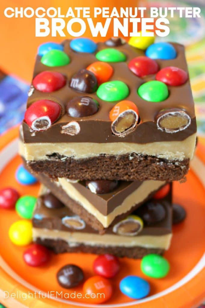 Chocolate peanut butter brownies topped with peanut butter M&M's, stacked on a plate. Buckeye brownies on a plate.