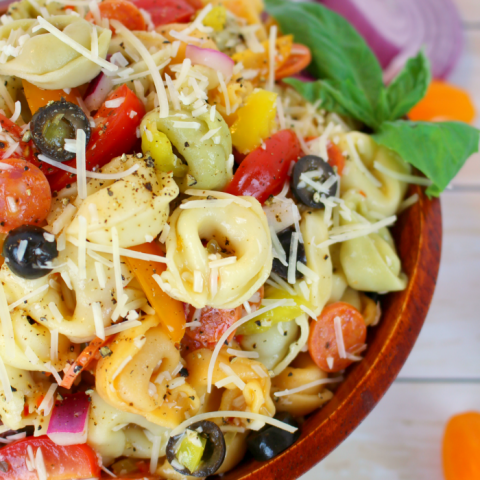 The perfect pasta salad for any pot-luck, picnic, cookout or backyard barbecue! This delicious tortellini salad is loaded with all of your Italian favorites, like salami, tomatoes, olives, banana peppers, red onion, and topped with Italian dressing and shredded Parmesan cheese! The ultimate side dish for any meal!