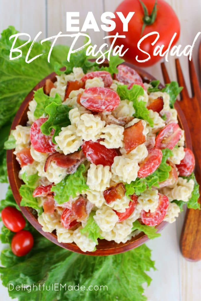 Overhead photo of ranch blt pasta salad with tomato garnishes and wooden salad utensils.