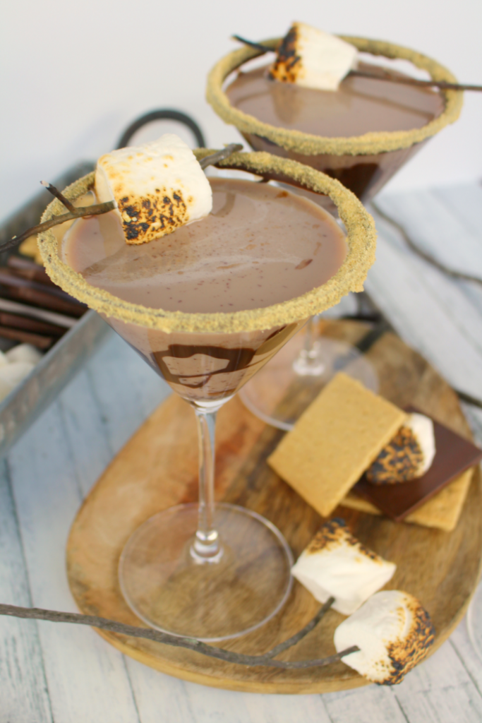 All the amazing flavors of s'mores in one glorious cocktail!  This fantastic summer cocktail is made with marshmallow vodka, creme de cocoa, along with graham cracker crumbs, and toasted marshmallows.  This drink will take you back to fun campfire memories, without the sticky fingers!