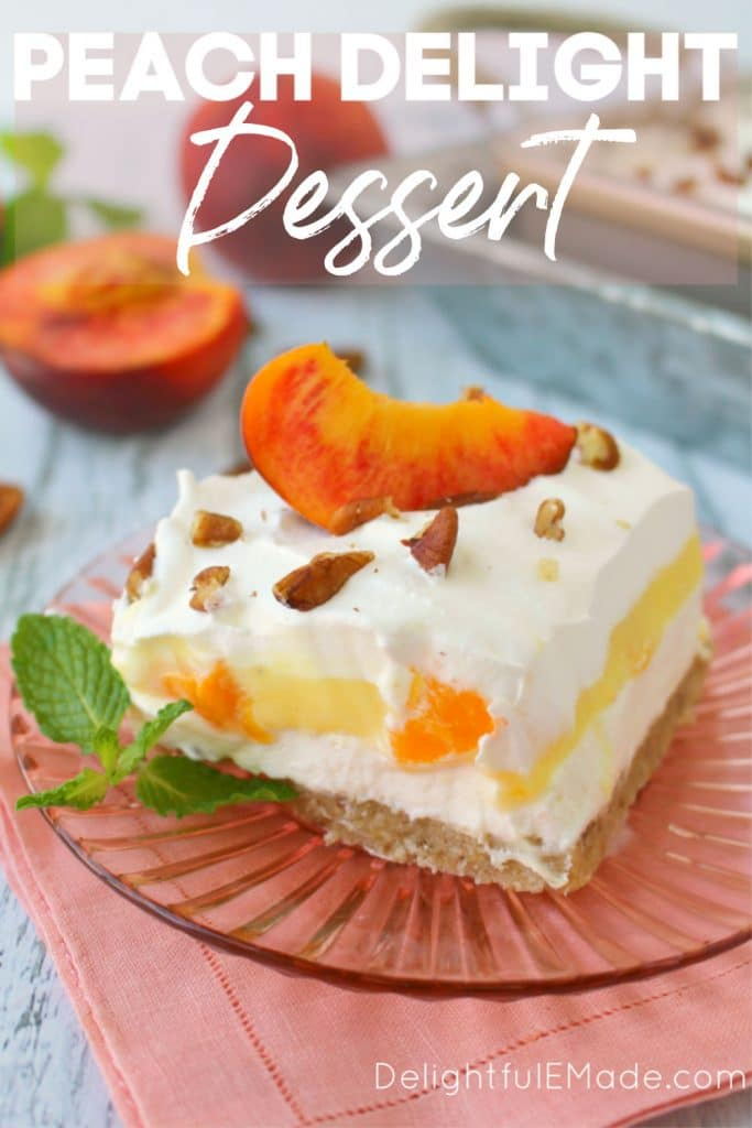 Peach delight dessert sliced into a square, plated and topped with a fresh peach slice and a mint sprig on the side.