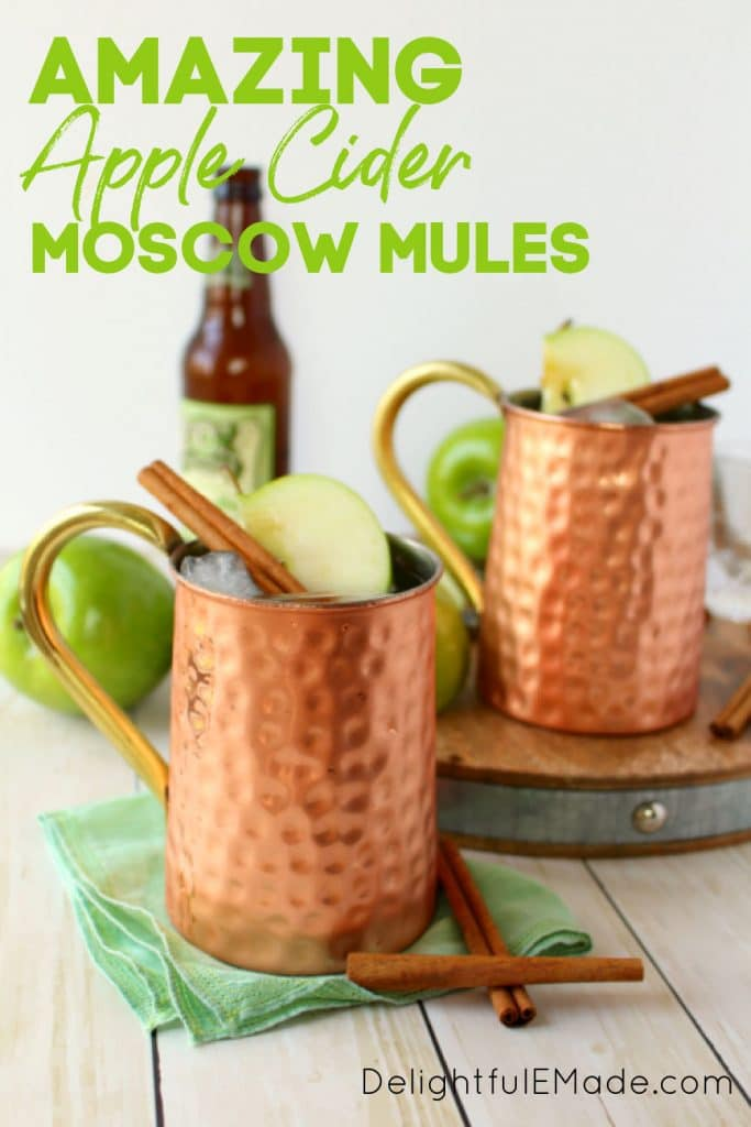 Apple Cider Moscow Mules, in copper mugs, garnished with apple slices and cinnamon sticks.