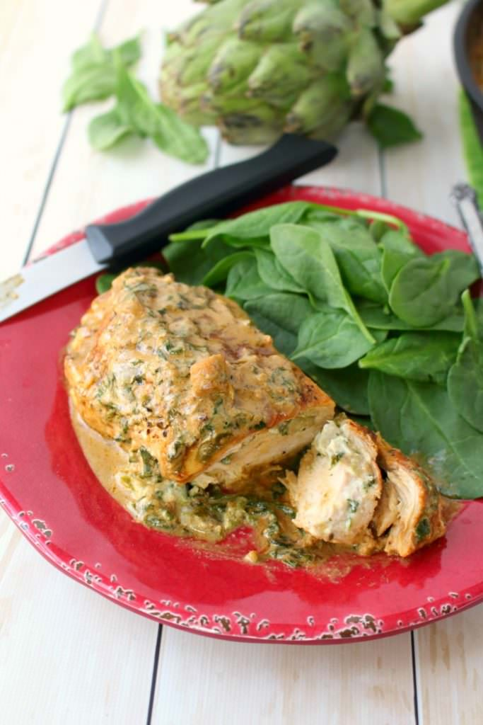 Let me introduce you to your new favorite chicken recipe!  This easy one skillet meal has all the flavors of Spinach and Artichoke Dip simmered together and stuffed into simple chicken breasts.  Incredibly flavorful, this delicious entree is the perfect dinner idea any night of the week!