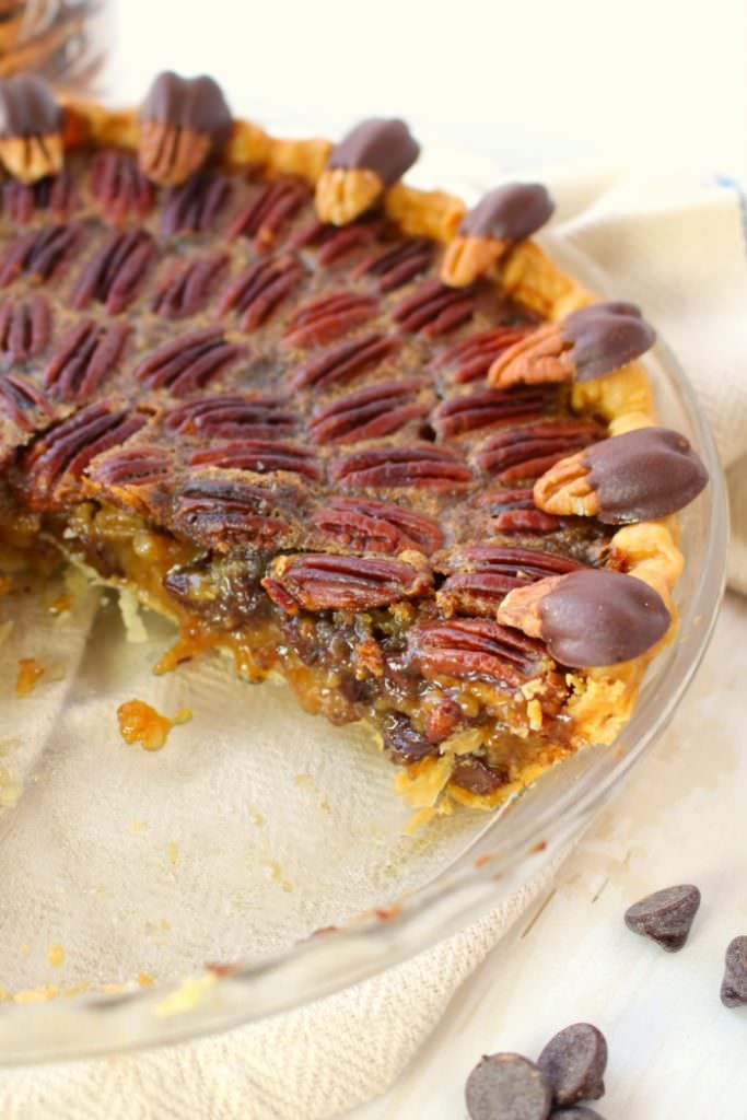 Your favorite pie recipe made even more decadent and delicious!  This Dark Chocolate Pecan Pie recipe is topped with chocolate covered pecans for a show-stopping dessert and is perfect for your Thanksgiving or Christmas dessert table!