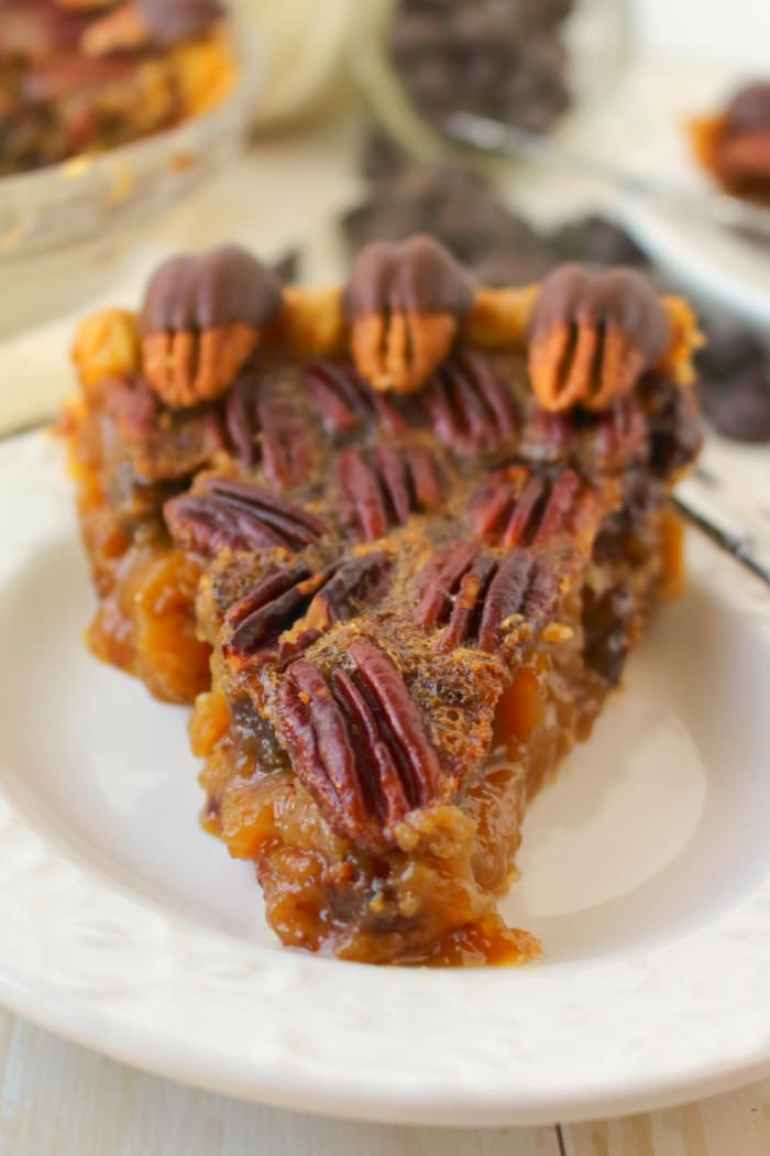 Your favorite pie recipe made even more decadent and delicious! Dark chocolate is added to this pecan pie recipe and topped with chocolate covered pecans for a show-stopping dessert! This pie is perfect for your Thanksgiving or Christmas dessert table!