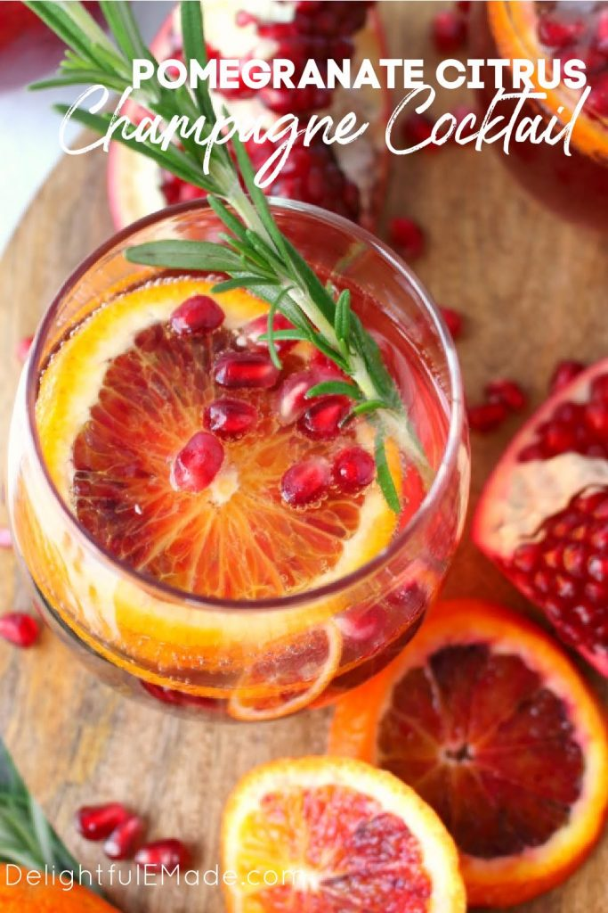 Pomegranate cocktail with champagne, sprig of rosemary and blood orange