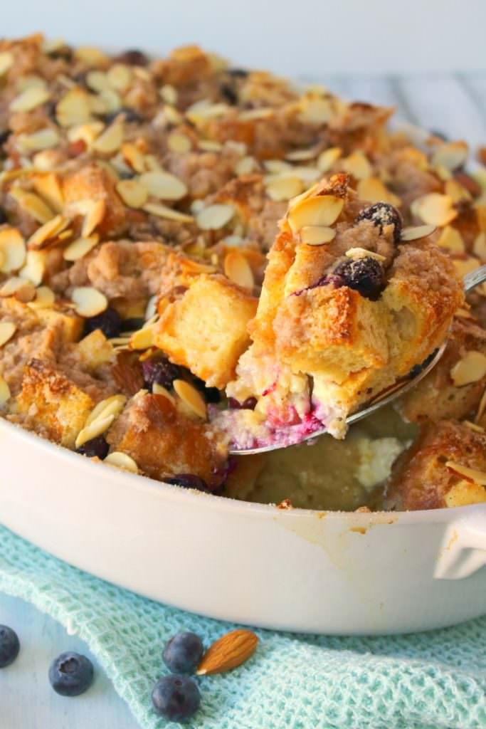 The ultimate baked French toast recipe! Blueberries and cream cheese are stars of this easy French toast casserole, which is topped with a cinnamon almond streusel and baked to perfection. Serve with blueberry syrup and whipped cream for the most amazing breakfast ever!