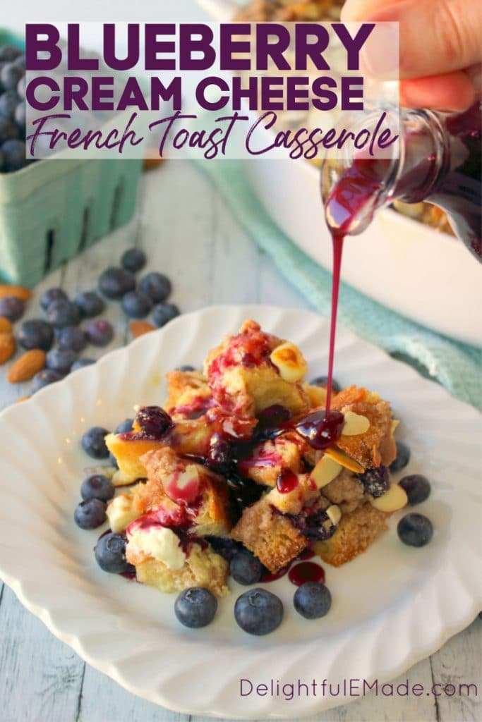 Blueberry French toast casserole on a small plate, topped with fresh blueberries and syrup being poured over the top.
