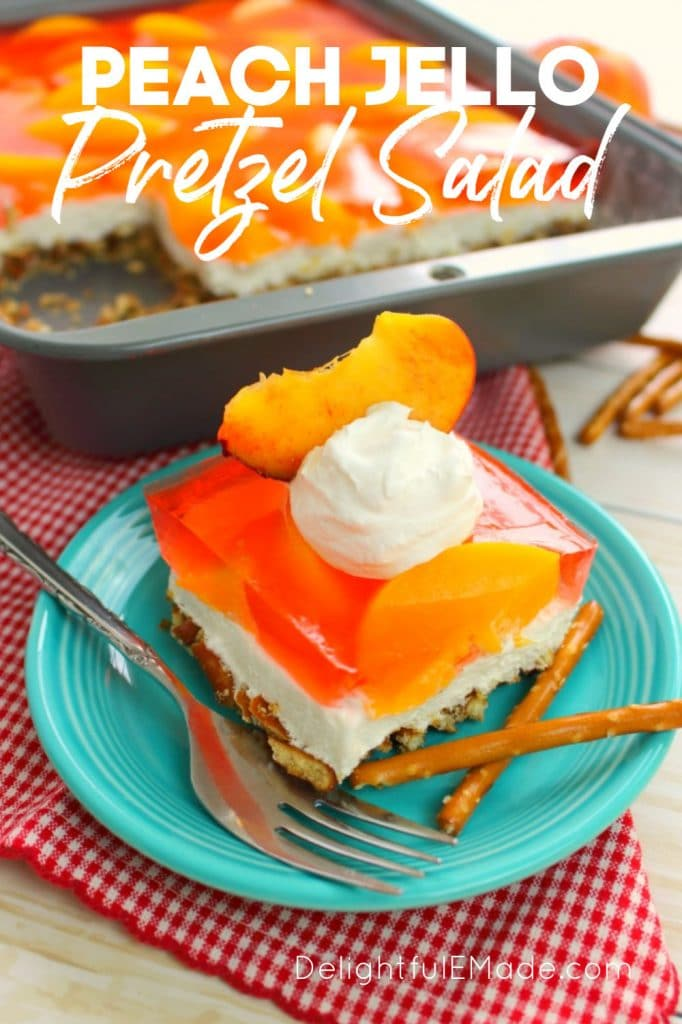 Peach Jello pretzel salad, sliced into a square on a plate, with whipped cream and peach slice on top.
