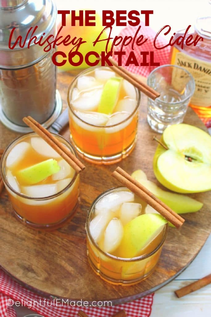 Three glasses of whiskey apple cider cocktail, garnished with yellow apple slices and cinnamon sticks.