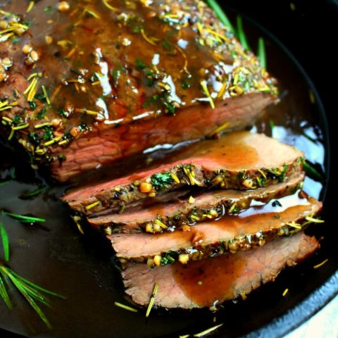 This Garlic Herb Roast Beef is fancy enough for your Christmas dinner, and simple enough for a Sunday supper. Oven roasted with a garlic herb rub, and topped with an amazing red wine sauce, this roast beef recipe is one you'll make all year long!