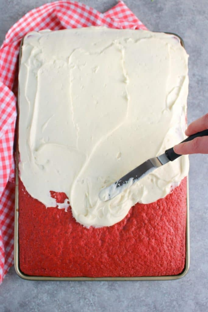 This scrumptious Red Velvet Sheet Cake recipe will be your new favorite way to do cake! Topped with a thick, delicious layer of cream cheese frosting, this easy red velvet cake recipe is incredible!