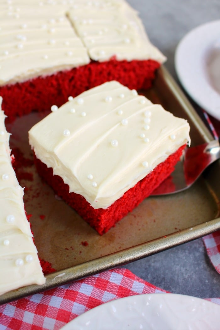 This scrumptious Red Velvet Sheet Cake recipe will be your new favorite way to do cake! Topped with a thick, delicious layer of cream cheese frosting, this homemade sheet cake recipe is incredible!