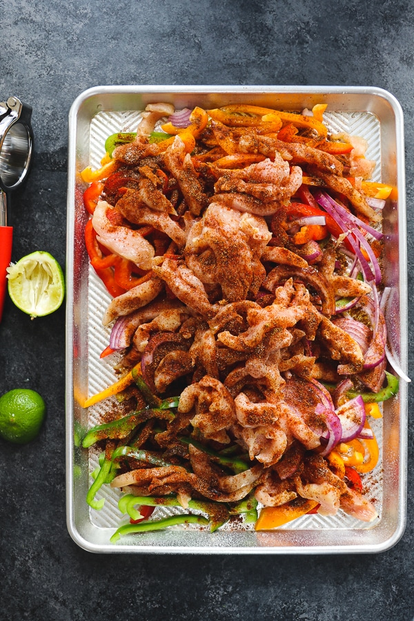 Looking for a simple, healthy chicken dinner idea? These Sheet Pan Chicken Fajitas are an amazing option! Loaded with fresh bell peppers and onions and made with simple chicken breasts, these baked chicken fajitas are perfect for when you're in the mood for Tex-Mex!