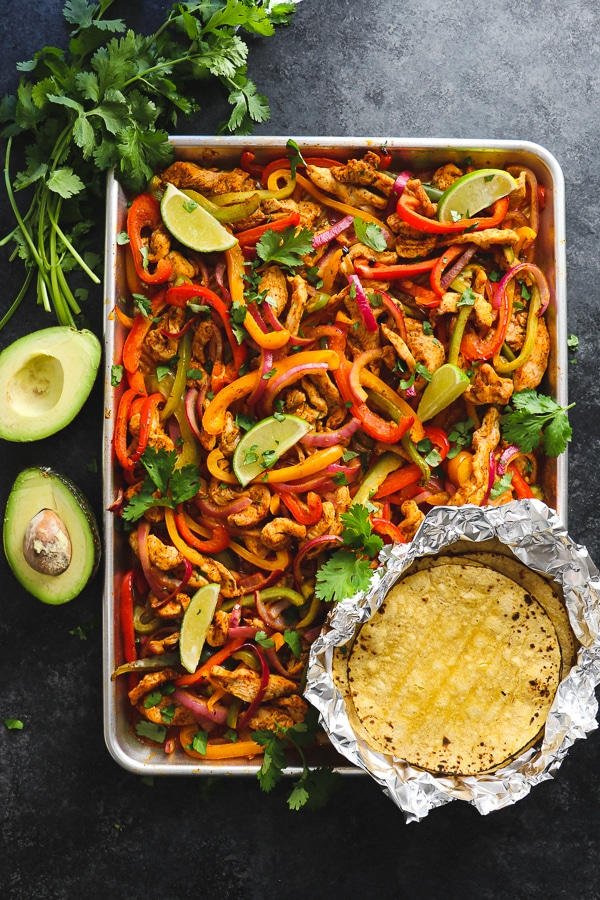 Looking for a simple, healthy chicken dinner idea? These Sheet PanChicken Fajitas are an amazing option! Loaded with fresh bell peppers and onions and made with simple chicken breasts, these baked chicken fajitas are perfect for when you're in the mood for Tex-Mex!