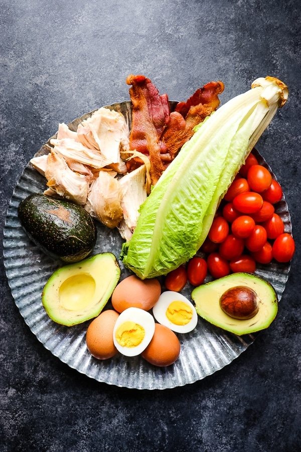 This healthy chicken cobb salad recipe is nothing short of incredible! With traditional cobb salad ingredients, this healthy version leaves out unhealthy oils and over-sugared dressings, but keeps all of the delicious flavors. I'll show you how to make cobb salad for meal prep, too!