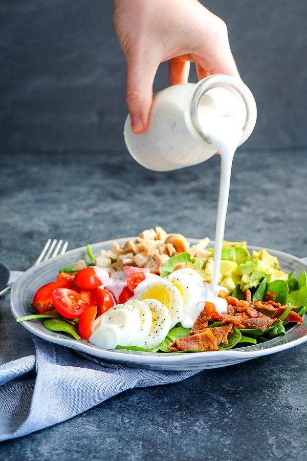 healthy Greek yogurt ranch dressing being poured over salad.
