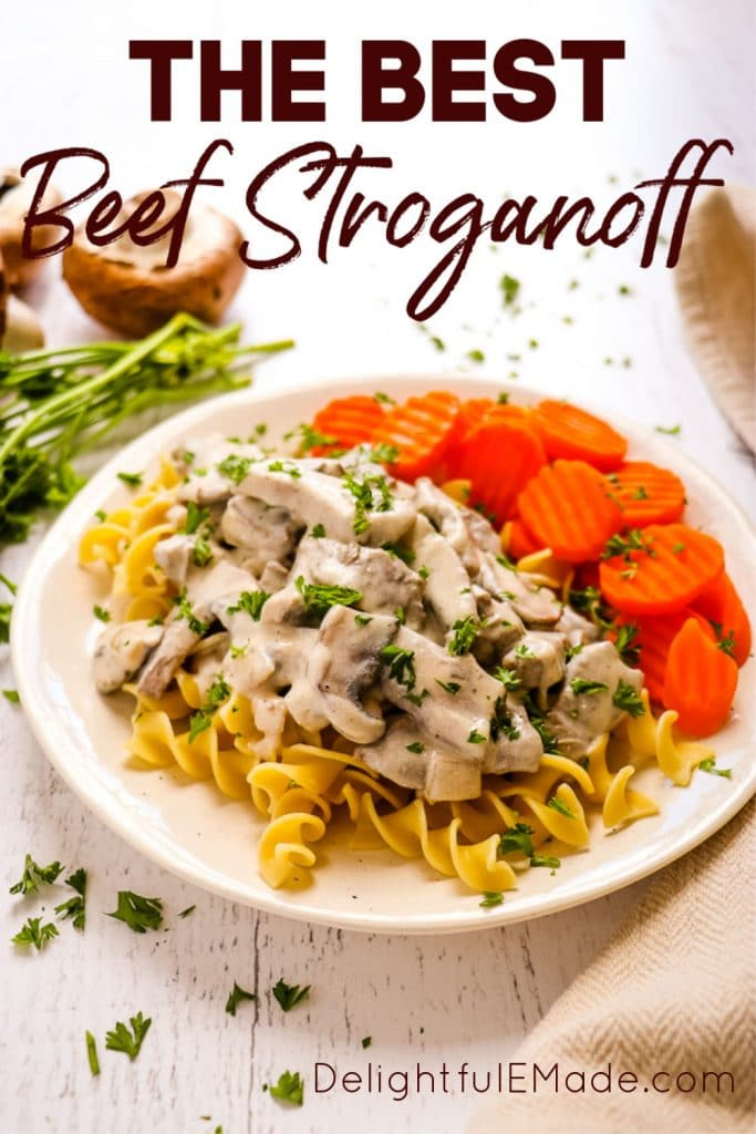 Classic Beef Stroganoff, on a plate with egg noodles, sliced carrots and sprinkled with green parsley.