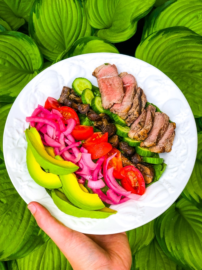 Pickled red onions on steak salad with avocados, tomatoes, mushrooms and cucumbers.