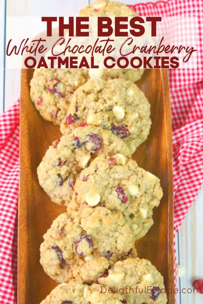 White chocolate cranberry oatmeal cookies on a wooden platter with extra cranberries and white chocolate chips as a garnish.