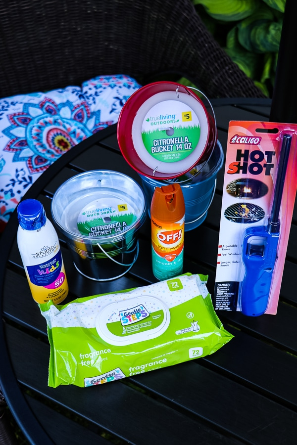 Patio table with summer items, lighter, bug spray, citronella candles, suncreen, lighter and baby wipes.