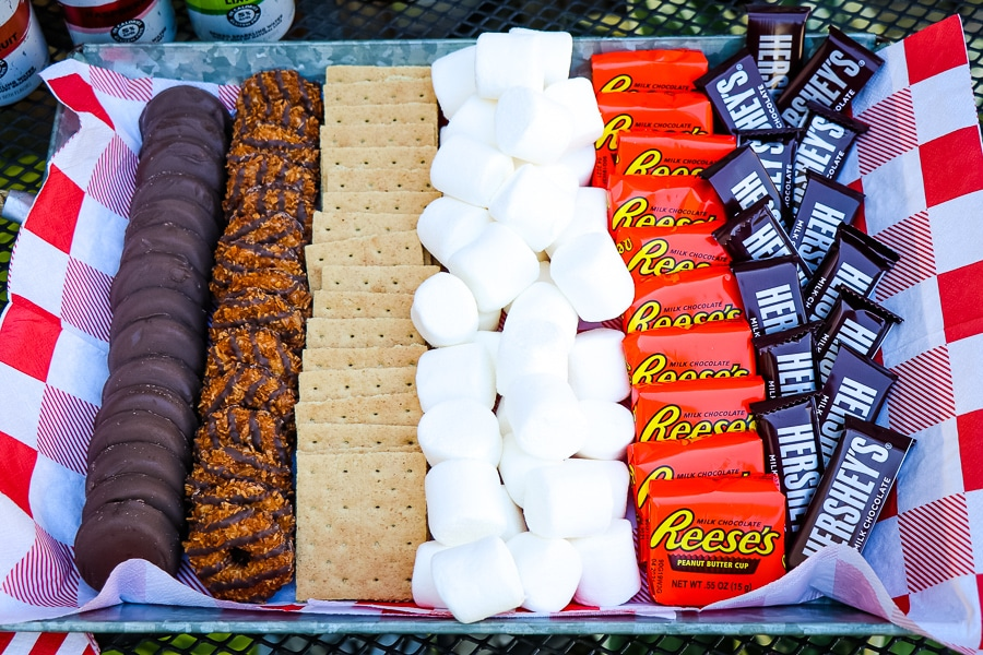 Tray of smores ingredients; marshmallows, chocolate bars, graham crackers, chocolate bars, peanut butter cups and cookies.