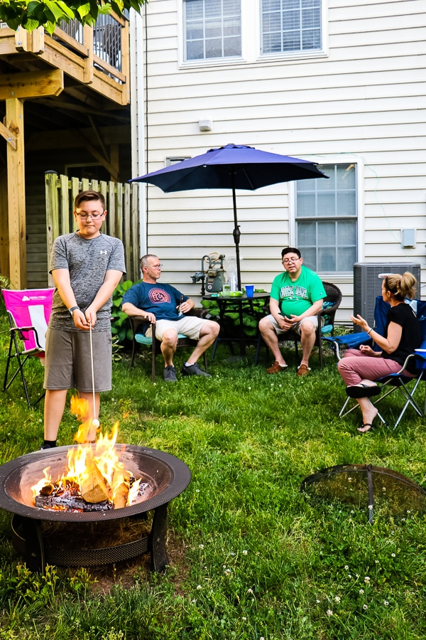 Family sitting in back yard talking while kid roasts a marshmallow at the fire pit.