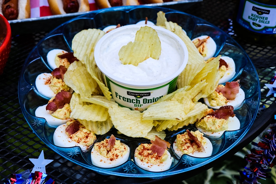 Tray of deviled eggs along with french onion dip and potato chips.