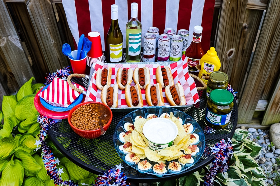 Table of cookout food; hot dogs, condiments, deviled eggs, baked beans, wine and hard seltzer. Patriotic decor and red, white and blue tableware.
