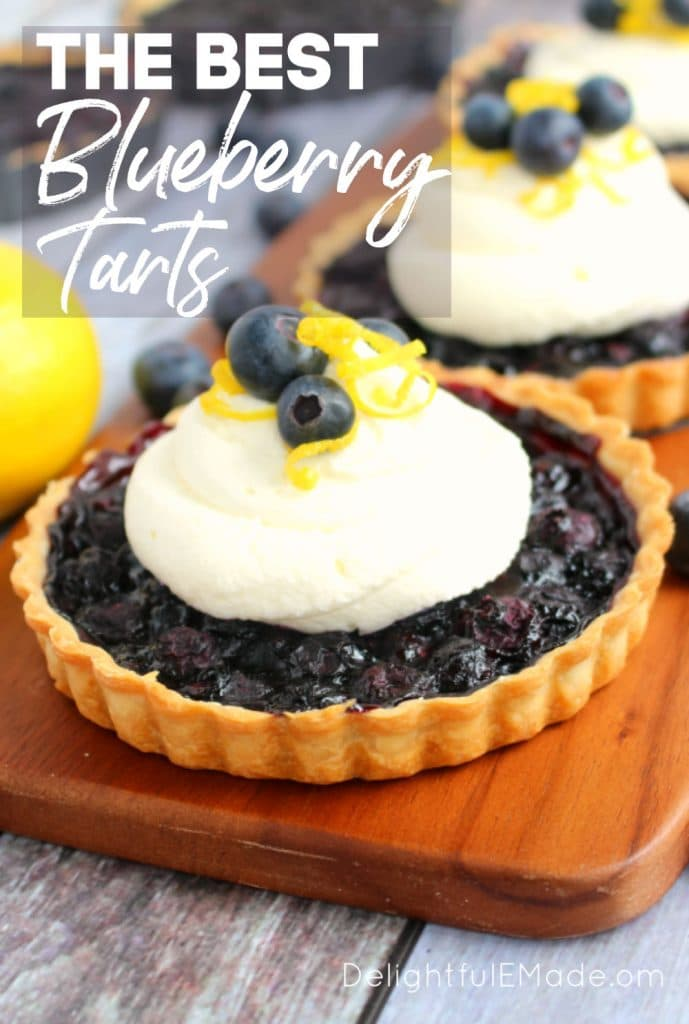 Single blueberry tart topped with lemon mascarpone cream and garnished with fresh blueberries and lemon zest.