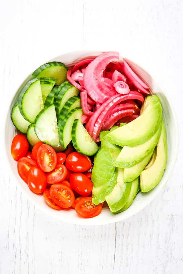 Bowl of sliced tomatoes, avocados, cucumbers and pickled red onions.