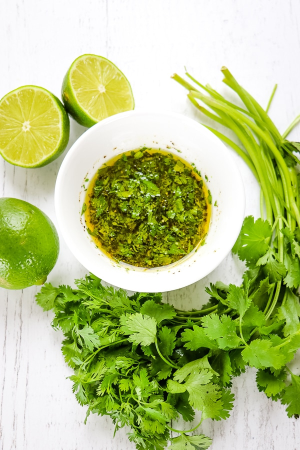 White bowl of cilantro lime dressing with sliced limes and sprigs of cilantro.