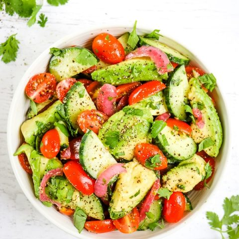 Cucumber tomato avocado salad with cilantro lime dressing and topped with ground pepper