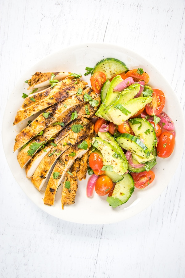 Plate with grilled chicken and cucumber tomato avocado salad all topped with chopped cilantro.