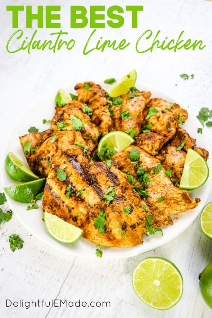 Grilled cilantro lime chicken on white plate with lime wedges and chopped cilantro on top.