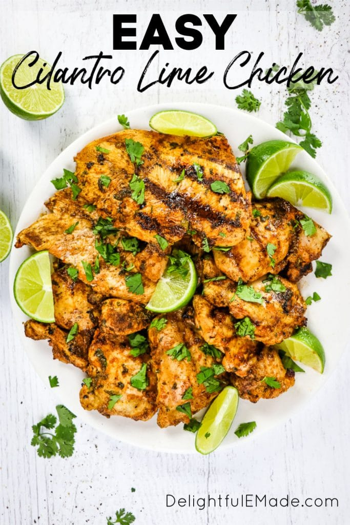 Plate of grilled cilantro lime chicken with lime wedges and chopped cilantro.